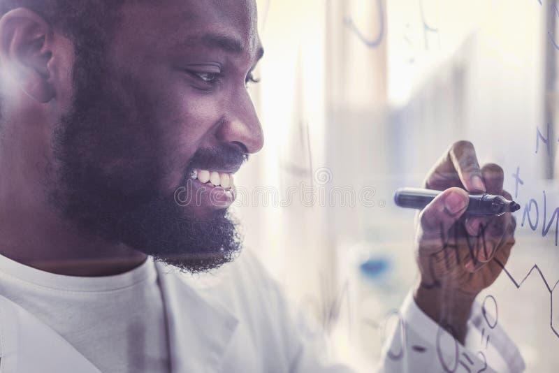 Молодой технолог усмехаясь пока пишущ химическую формулу стоковая фотография rf