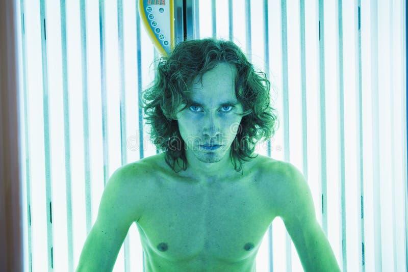 Молодой тонкий человек на солярии в салоне красоты стоковые фотографии rf