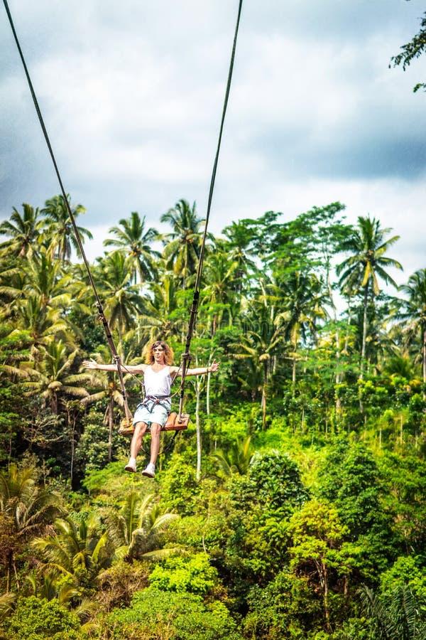 Молодой туристский человек при длинные волосы отбрасывая на скале в тропическом лесе джунглей тропического острова Бали стоковые изображения rf