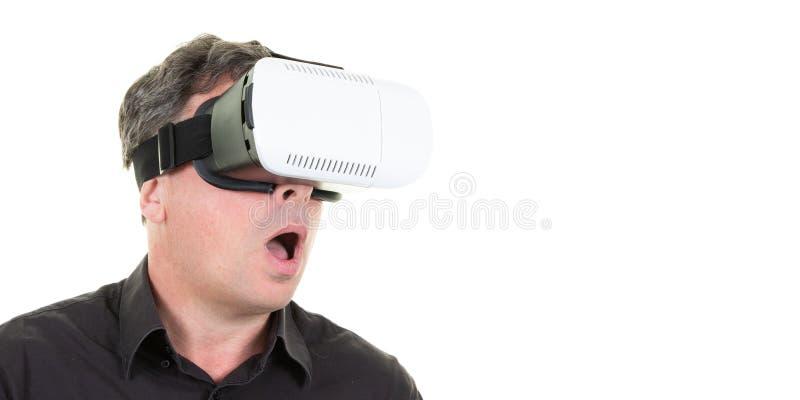 Молодой удивленный человек со шлемофоном vr на белом космосе экземпляр стоковые фотографии rf