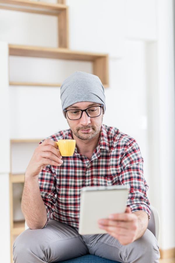 Молодой ультрамодный человек сидя на офисе и наслаждаясь его кофе утр стоковое изображение rf