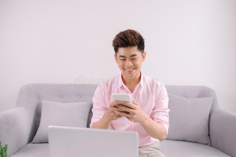 Молодой усмехаясь азиатский человек сидя на кресле отправляя SMS пока работающ o стоковые изображения
