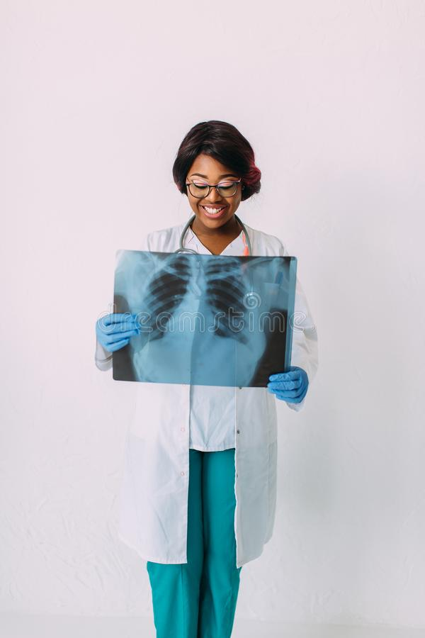 Молодой усмехаясь Афро-американский доктор женщины в медицинских одеждах держа рентгеновский снимок пациента стоковые фотографии rf