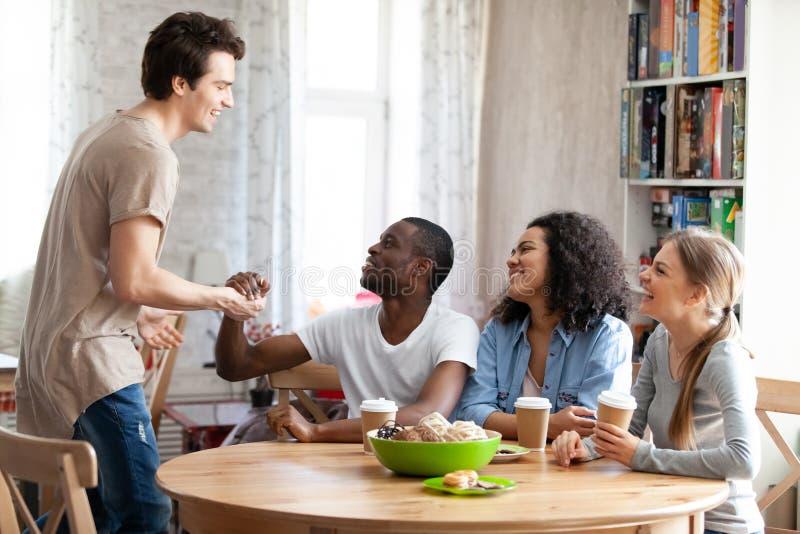 Молодой усмехаясь Афро-американский человек приветствуя как раз пришел друг стоковые фотографии rf