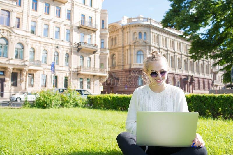 Молодой усмехаясь студент женщины уча на-линию через портативный компьютер, сидя на университетском кампусе стоковое фото