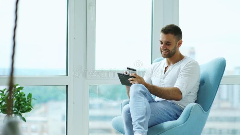 Молодой усмехаясь человек делая онлайн покупки используя цифровой планшет сидя на балконе в современной квартире просторной кварт стоковое фото