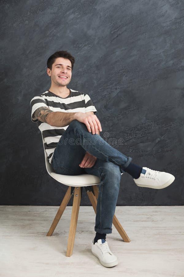 Молодой усмехаясь человек сидя на серой предпосылке студии стоковое изображение