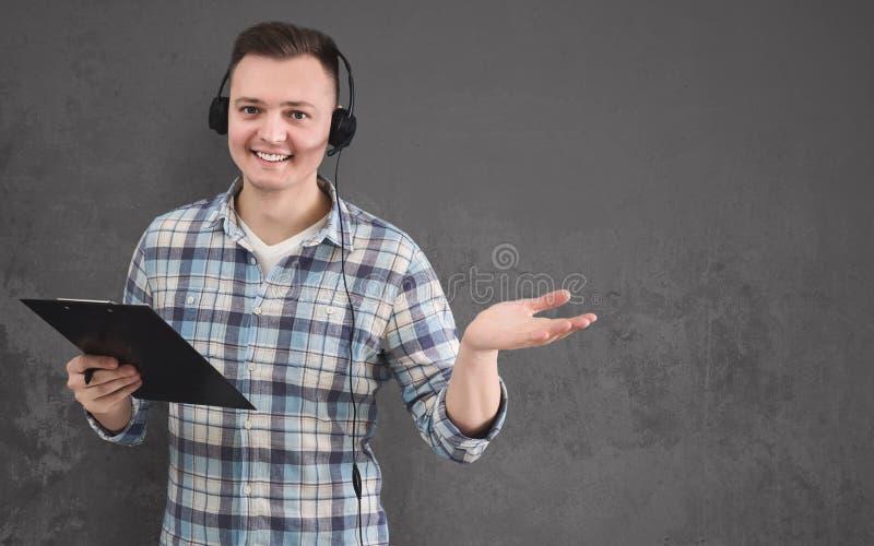 Молодой усмехаясь человек со шлемофоном, космосом экземпляра стоковое фото rf