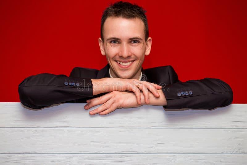 Молодой усмехаясь человек с пустой красной доской знака стоковое фото