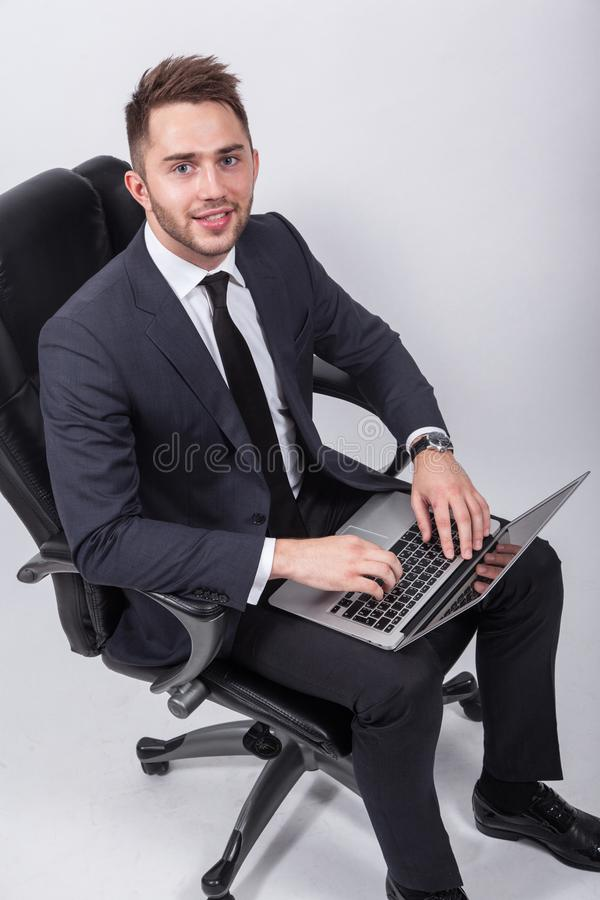 Молодой успешный бизнесмен сидя в стуле офиса на whi стоковое изображение
