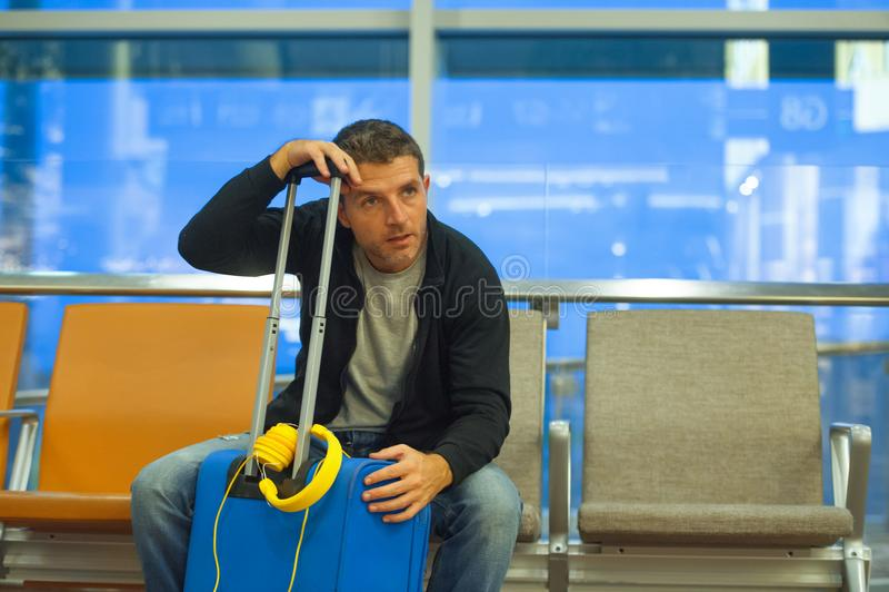 Молодой утомленный туристский человек в авиапорте с усаживанием чемодана потревоженном и усиленном на стробе восхождения на борт  стоковое фото rf