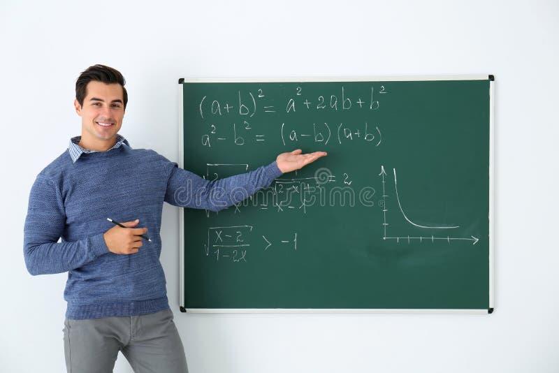 Молодой учитель объясняя формулы математики написанные на доске стоковое фото rf