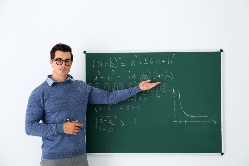 Молодой учитель объясняя формулы написанные на доске в классе стоковые изображения