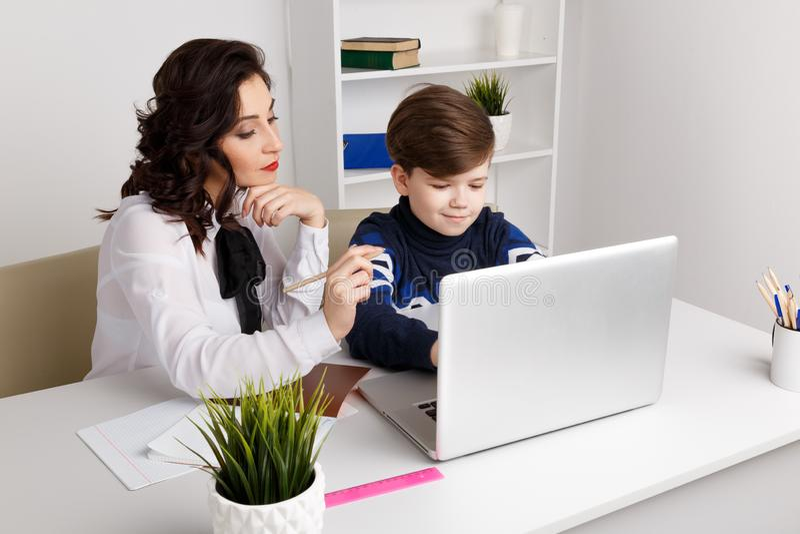 Молодой учитель с ребенк делая домашнюю работу на компьютере Помощь гувернера стоковая фотография rf