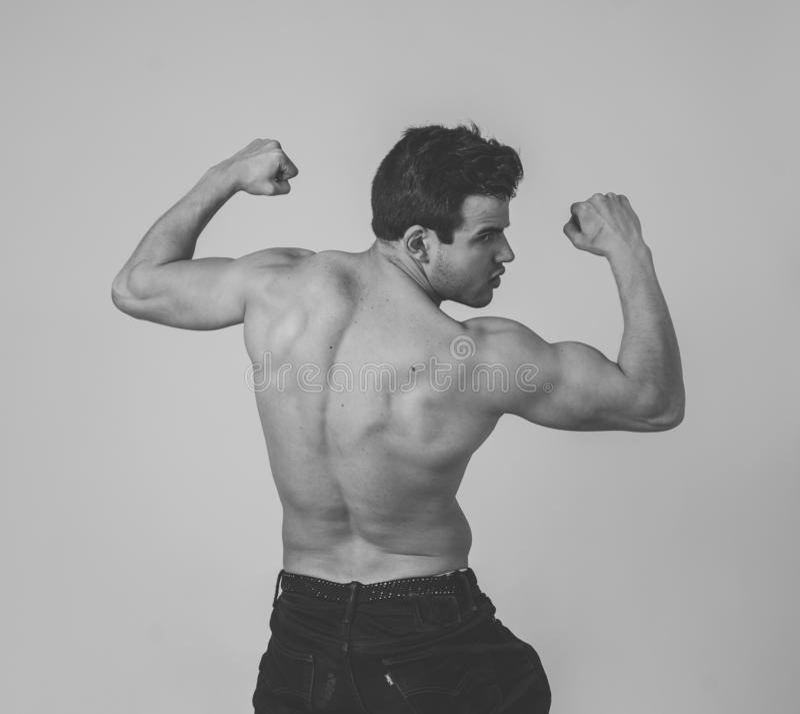 Молодой фитнеса человек muscly показывая его мышцы назад, плеч, трицепса и бицепса после тренировки стоковое фото rf