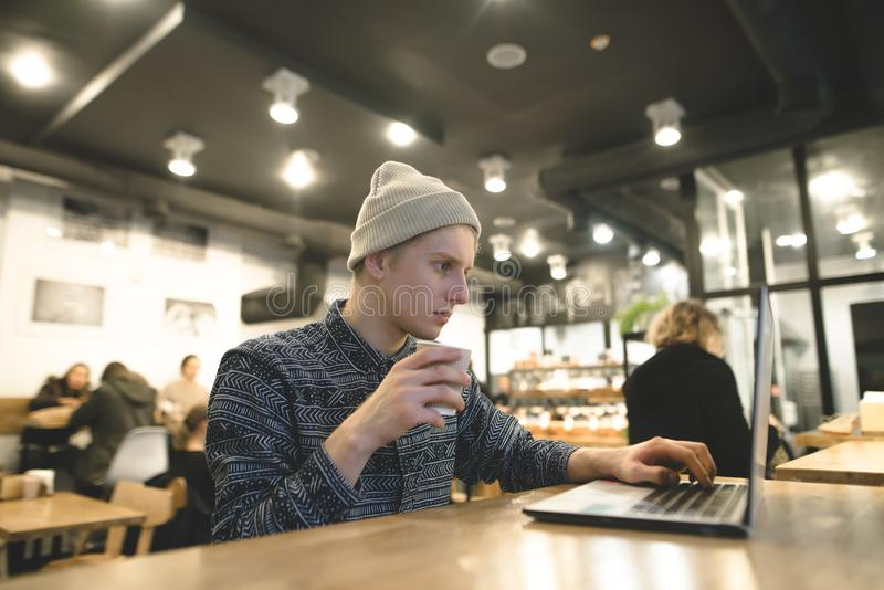 Молодой фрилансер работает для компьтер-книжки в сочном кафе и выпивает кофе Студент битника на компьютере в кафе стоковое фото