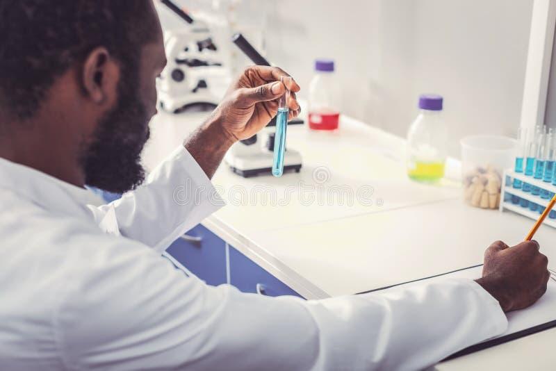Молодой химик нося равномерную валовую формулу сочинительства стоковые фотографии rf
