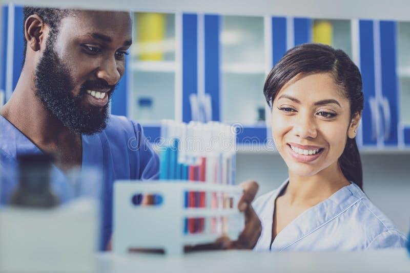Молодой химик соединяя ее парня в лаборатории стоковые фото