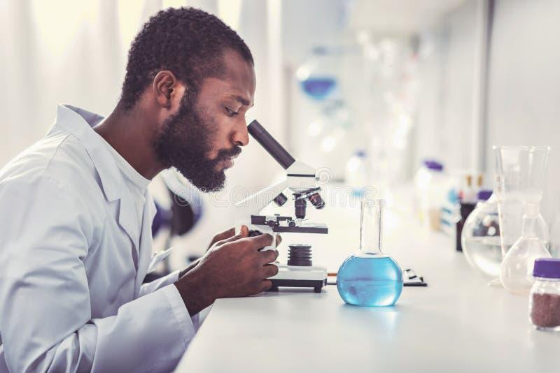 Молодой химический практикующий врач смотря в микроскоп стоковое фото rf