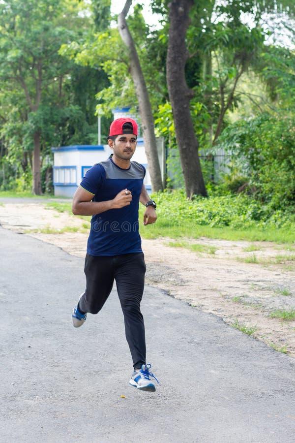 Молодой ход спортсмена в земле спорт на дороге стоковые фото
