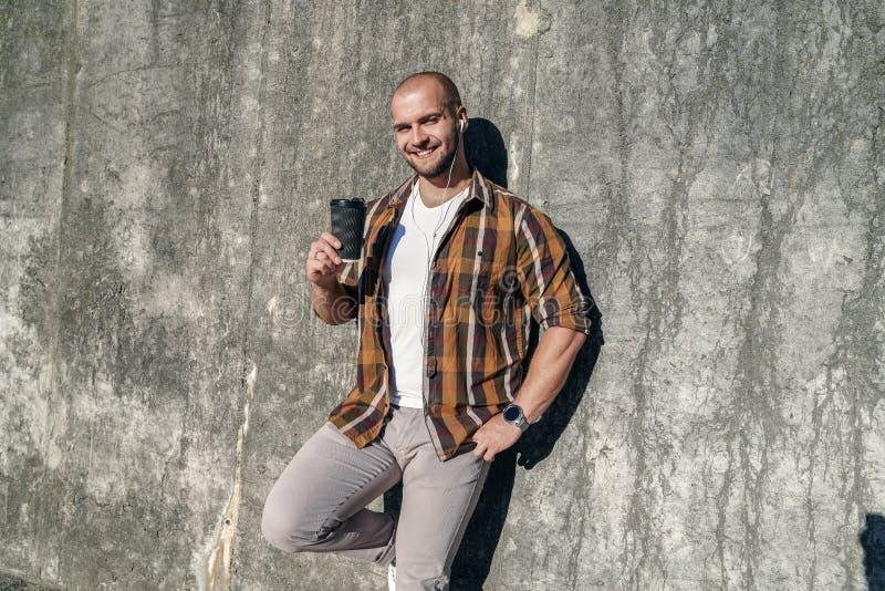Молодой хороший выглядя смелый бородатый фрилансер стоя outdoors против серой современной стены просторной квартиры держа кофе в  стоковое фото