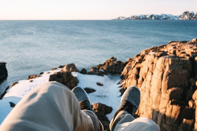 Молодой храбрый путешественник отдыхая на утесе перед снежной скалой и голубым океаном и взгляде на ногах Взгляд POV на ногах и б стоковая фотография