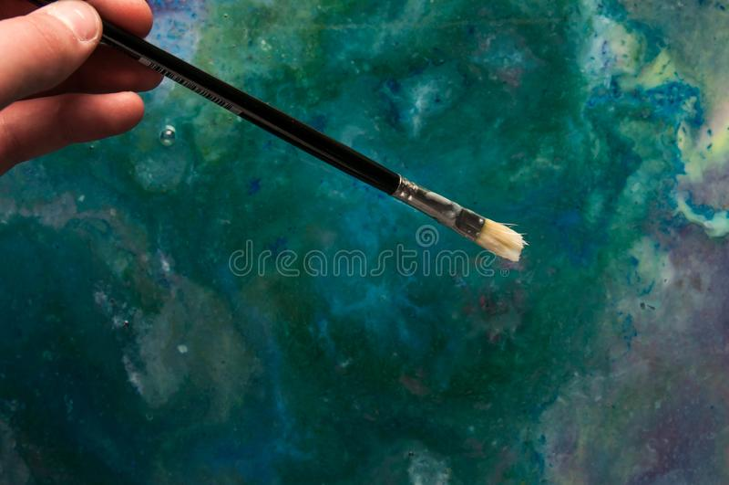 Молодой художник держа кисть, смесь красок масла на заднем плане стоковые фотографии rf