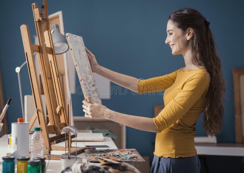 Молодой художник кладя холст на мольберт стоковая фотография