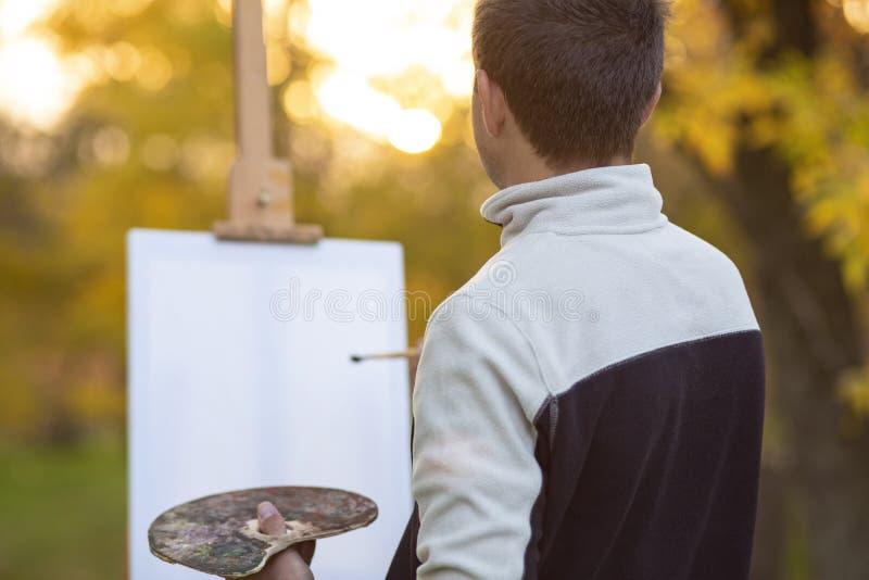 Молодой художник красит изображение на холсте на мольберте в природе, человеке с щеткой и палитра красок среди деревьев осени, стоковая фотография