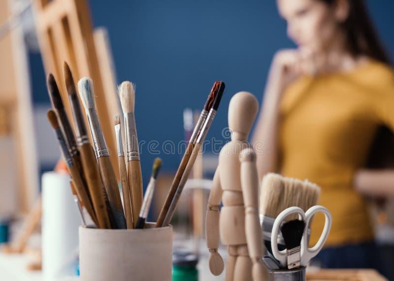 Молодой художник наблюдая ее картину на мольберте стоковые фотографии rf
