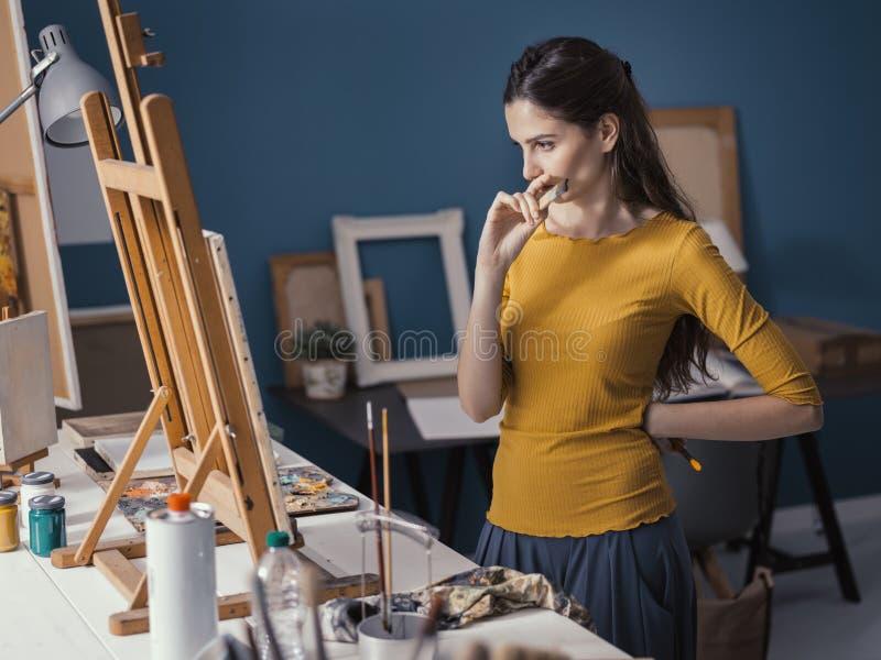 Молодой художник наблюдая ее картину на мольберте стоковая фотография