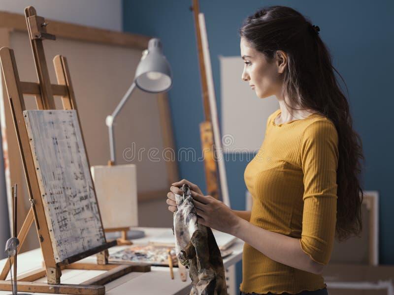 Молодой художник очищая ее руки с тканью стоковые фотографии rf
