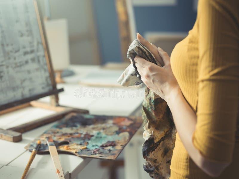 Молодой художник очищая ее руки с тканью стоковое фото