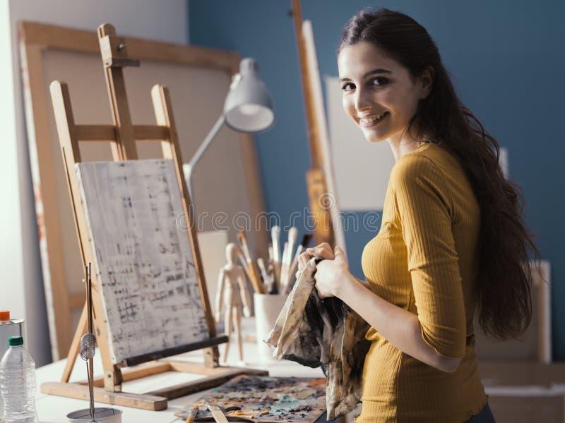 Молодой художник очищая ее руки с тканью стоковые изображения