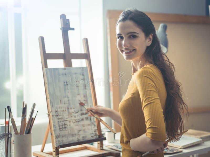 Молодой художник работая на абстрактной картине в atelier стоковое изображение