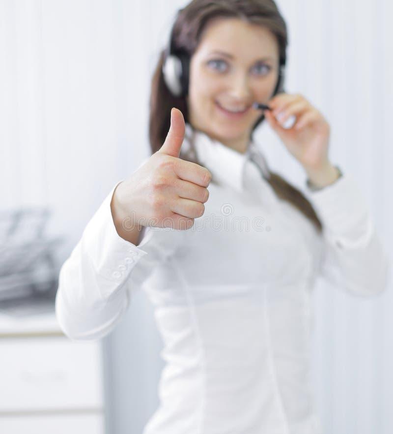 Молодой центр телефонного обслуживания работника показывая большой палец руки вверх стоковая фотография