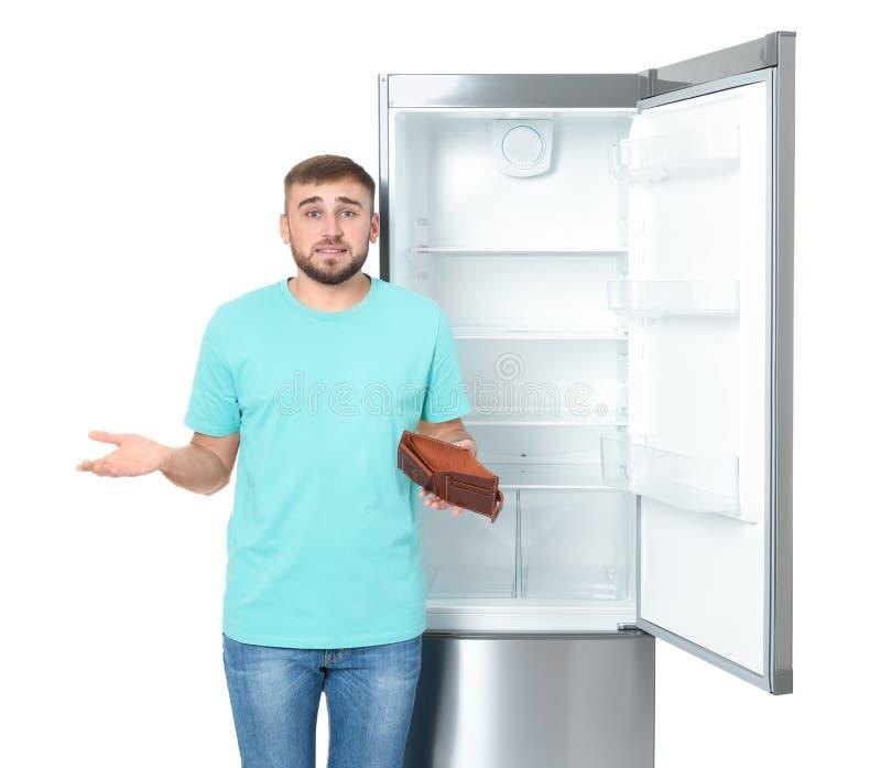 Молодой человек без денег в бумажнике около пустого холодильника на белой предпосылке стоковое изображение rf