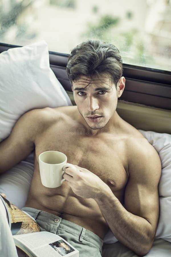 Молодой человек без рубашки на его кровати с чашкой кофе или чая стоковая фотография rf