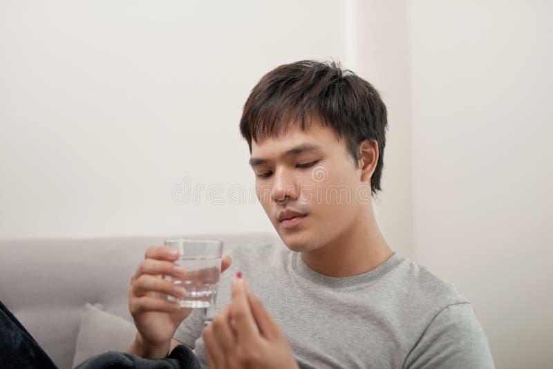 Молодой человек болен с гриппом, лежит дома под одеялом, взятием стоковое изображение rf