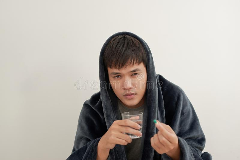 Молодой человек болен с гриппом, лежит дома под одеялом, принимает пилюльку стоковая фотография
