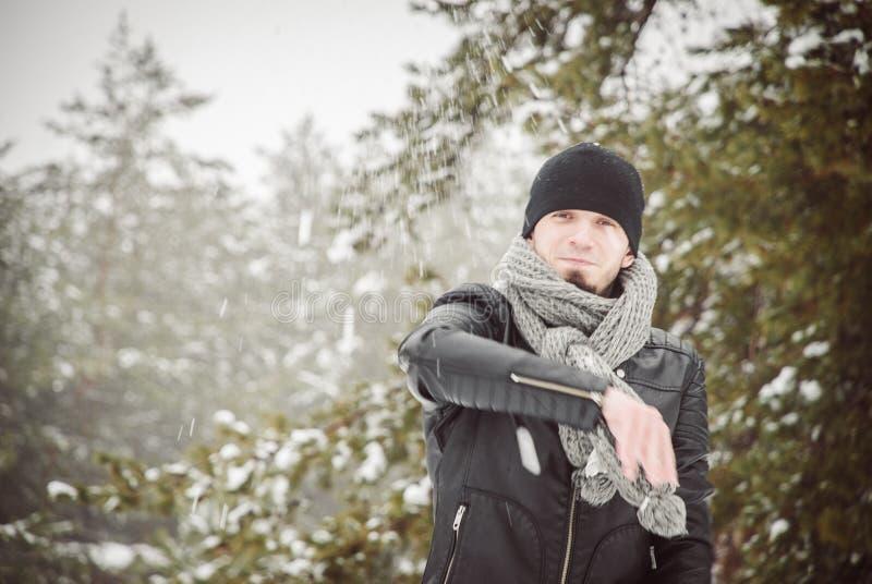 Молодой человек бросая снежный ком в лесе зимы стоковое фото rf