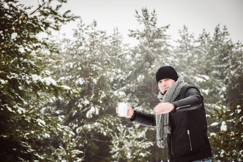 Молодой человек бросая снежный ком в лесе зимы стоковое фото