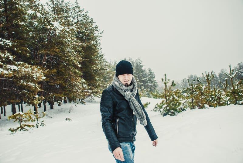 Молодой человек бросая снежный ком в лесе зимы стоковые изображения rf