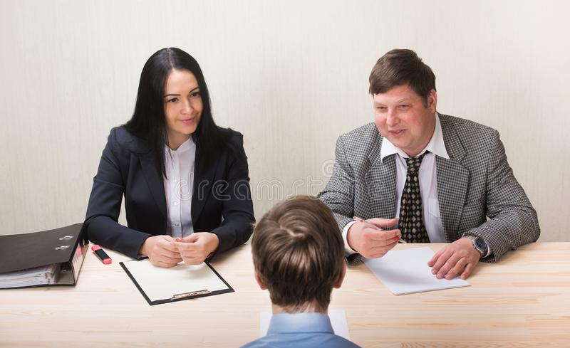 Молодой человек во время собеседования для приема на работу и членов managemen стоковое изображение