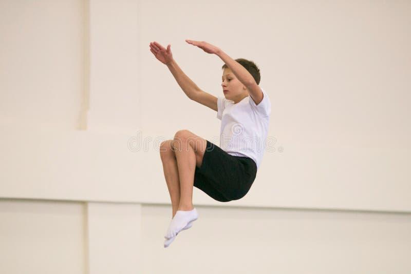 Молодой человек выполняет гимнастические тренировки в спортзале стоковое изображение