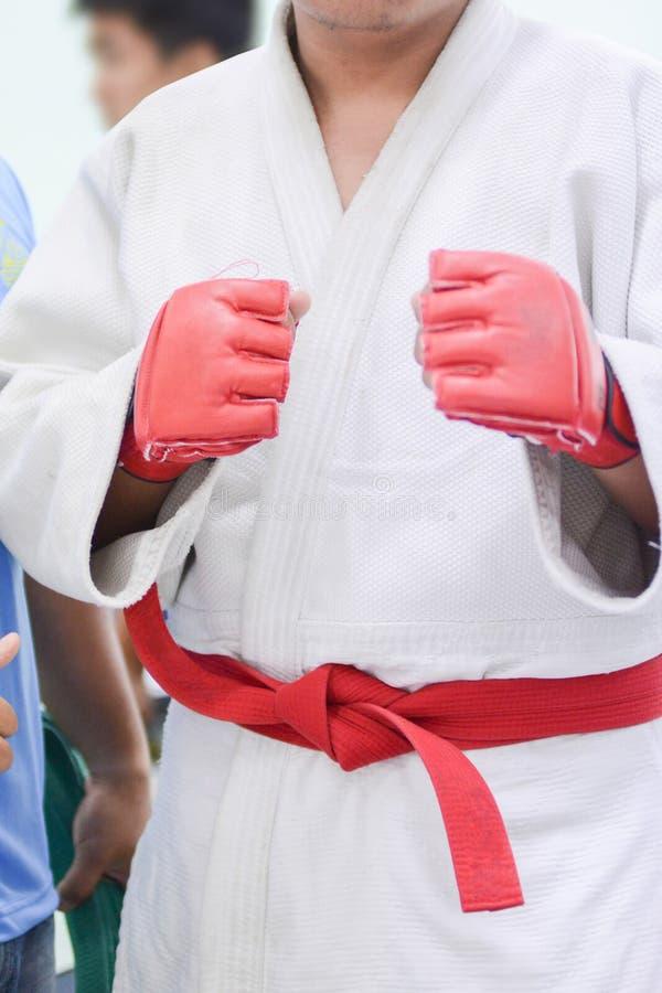 Молодой человек в белом кимоно для самбо, дзюдо, jujitsu представляя на белой предпосылке, смотря прямо, положение воюя столба, р стоковое изображение rf