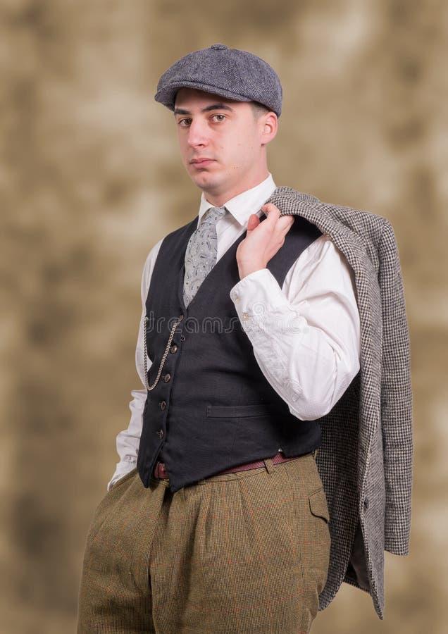 Молодой человек в винтажных одеждах с шляпой, стилем 1940 стоковое изображение