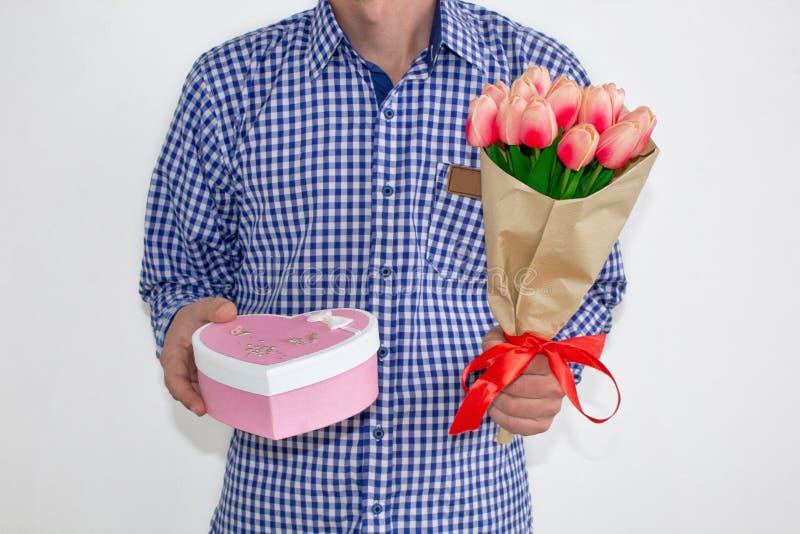 Молодой человек в голубой рубашке и джинсах шотландки, держащ букет тюльпанов и подарочной коробки в форме сердца, на белом backg стоковое изображение rf