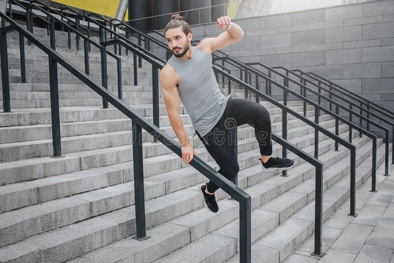 Молодой человек в движении Он держит одну руку на барьере и скачки над ним Он смотрит прямо Молодой человек скачет на лестницы Он стоковая фотография
