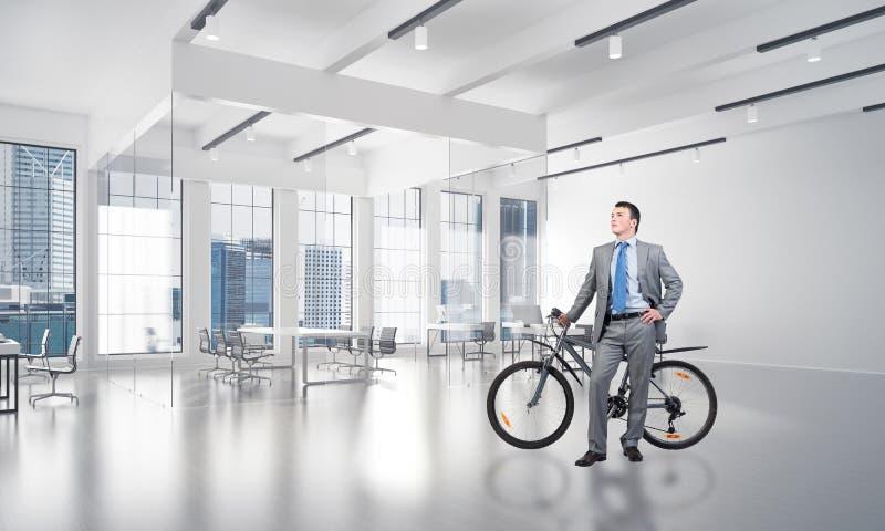 Молодой человек в деловом костюме с велосипедом стоковые фото